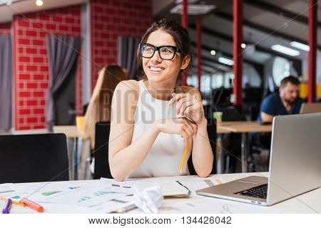 Portrait of smiling pretty young business woman in glasses sitting on workplace