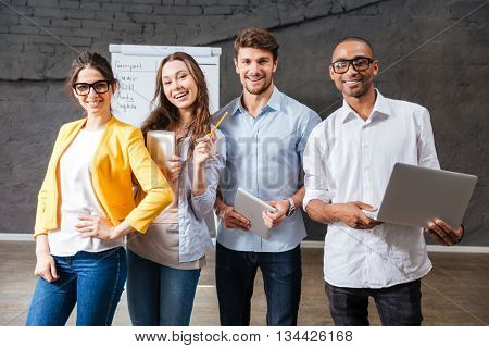 Group of cheerful successful young business people with tablet and laptop standing in conference room
