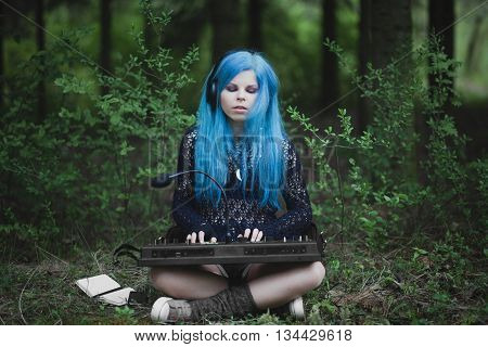 Young Girl With Blue Hair Playing Synthesizer Dressed In Black Sitting On Grass In Spring In Park. F