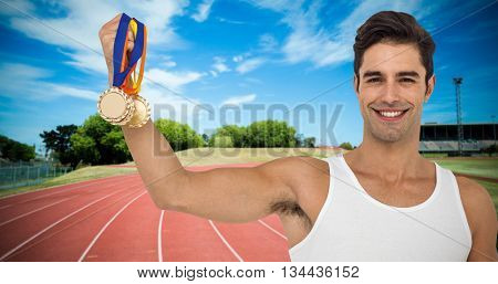 Athlete posing with gold medals on white background against high angle view of track