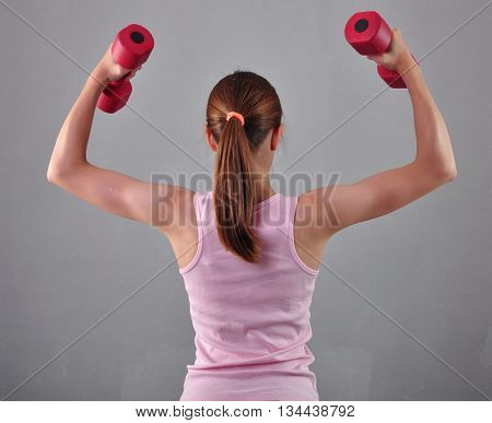 Teenage sportive girl is doing exercises with dumbbells to develop muscles on grey background. Sport healthy lifestyle concept. Sporty childhood. Teenager child exercising with weights.