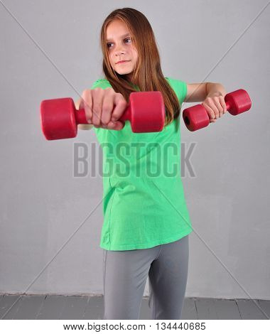 Teenage sportive girl is doing exercises with dumbbells to develop muscles isolated on grey background. Sport healthy lifestyle concept. Sporty childhood. Teenager exercising with weights.