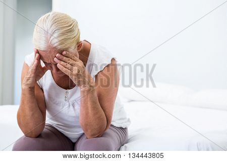 Upset senior woman with head in hand sitting on bed at home
