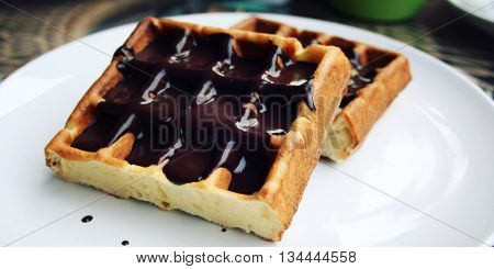 Vienna Waffles with chocolate topping. Aged photo. Delicious dessert. White plate with Chocolate covered Wafers. Toned. Delicious dessert. Wide photo for wallpaper or site slider.