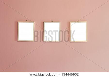 three blank wood  frame on pink wall