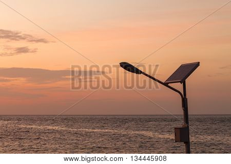 street light with solar panel against sea at sunset