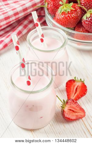 Strawberry milkshake in the glas jar with drinking straw on white wooden table