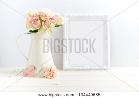 styled stock photograph of cream jug of flowers next to a white ornate frame. You can place your business promotion blog title quote headline or image in the frame.