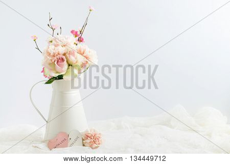 Mockup styled stock image of carnations roses & blossom in a cream jug with a piece of lace. You can place your business promotion blog title quote headline or image in the space beside the jug.