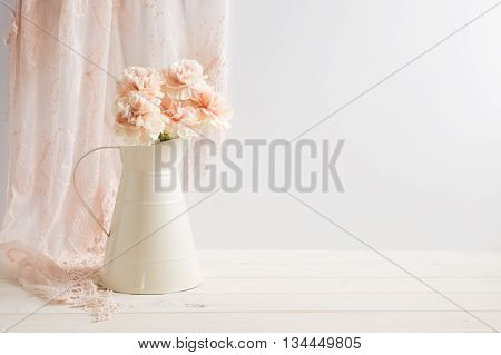 Mockup styled stock image of carnations in a cream jug with a piece of lace behind the jug. You can place your business promotion blog title quote headline or image in the space beside the jug.