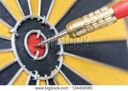 closeup dart arrow hitting in target bullseye of dartboard business data integration solutions and success concept