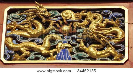Golden chinese dragon architectural details on a gate within Jingshan Park Beijing China.