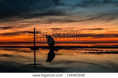Man kneeling in prayer by a black cross with a very warm Sunset sky behind him.