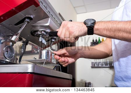 A handsome young man making coffee at the bar in a coffee shop