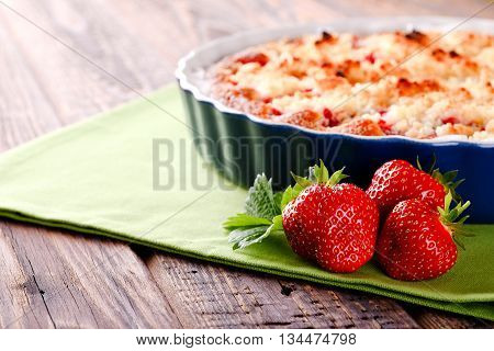 Three Fresh Red Strawberries In Front Of Fruit Pie On Green Towel