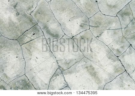 Cement floor with several cracks seen from above