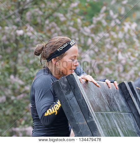 STOCKHOLM SWEDEN - MAY 14 2016: Beautiful women climbing over a plank obstacle in the obstacle race Tough Viking Event in Sweden May 14 2016