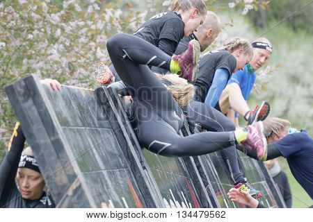 STOCKHOLM SWEDEN - MAY 14 2016: Women making a spectacular overturn when climbing over a plank obstacle in the obstacle race Tough Viking Event in Sweden May 14 2016