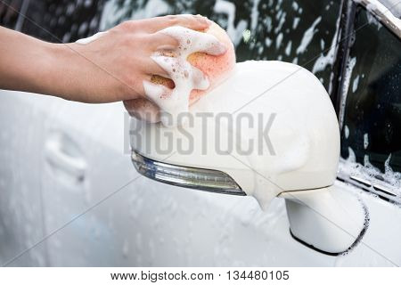 Male Hand Washing Car Mirror With Sponge