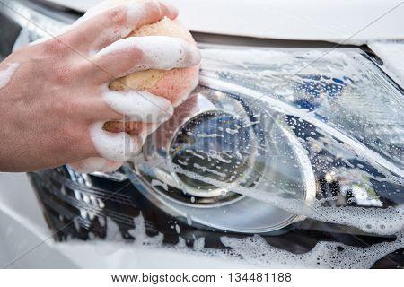 Handle Carwash Concept - Man Washing Car Headlamp With Sponge And Foam