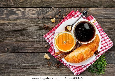 Continental breakfast - cup of hot coffee croissant and orange. Tasty food on plaid red napkin. Rustic wooden background. Top view place for text.