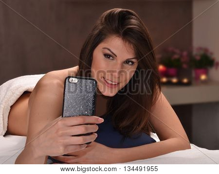 Woman taking selfie at beauty center, body treatment salon.