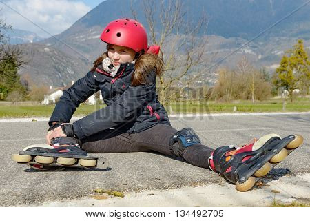young attractive teenage skater grimacing in pain after taking a fall