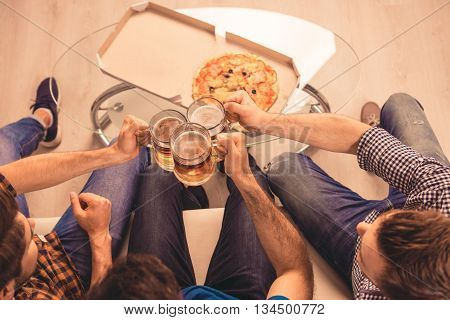 Cheers!  Top-view Photo Of  Men Celebrating And Clinking Glass Of Beer