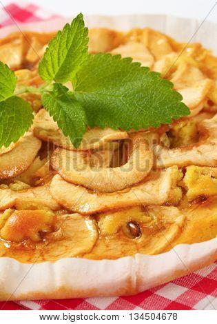 close up of homemade apple pie on checkered dishtowel