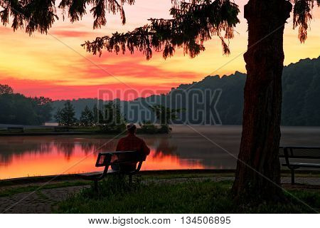A man enjoying a beautiful sunrise at Gifford Pinchot State Park in York County Pennsylvania USA.