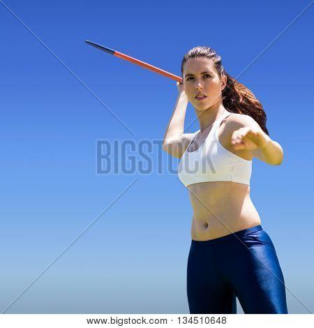 Woman throwing javeline against bright blue sky