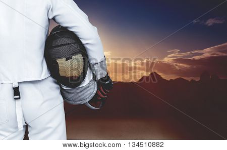 Rear view of swordsman holding fencing mask and sword against composite image of landscape