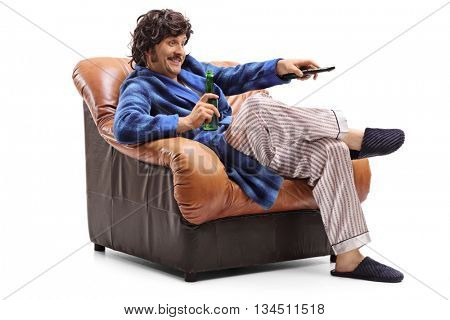 Young man sitting in an armchair with a beer in his hand and changing channels on TV isolated on white background