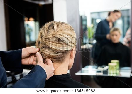 Closeup Of Hairdresser's Hands Braiding Client's Hair poster