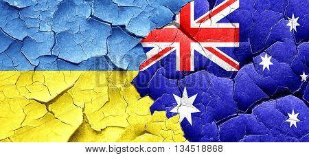 Ukraine flag with Australia flag on a grunge cracked wall