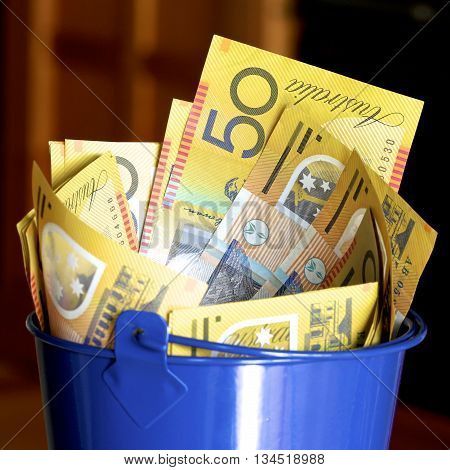 A blue bucket full of Australian fifty dollar notes.
