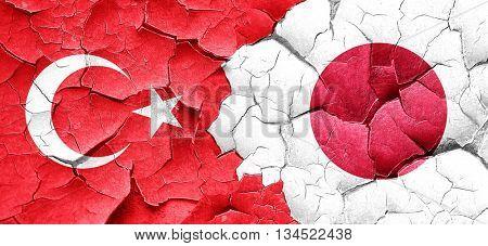 Turkey flag with Japan flag on a grunge cracked wall