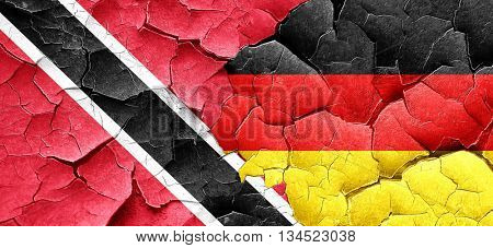 Trinidad and tobago flag with Germany flag on a grunge cracked w