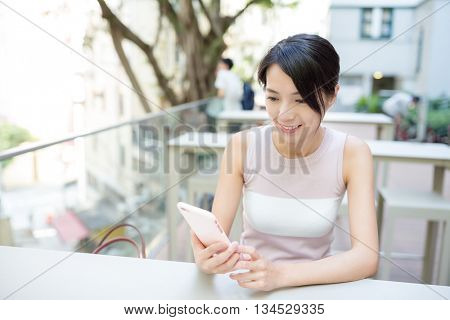 Asian woman send sms on mobile phone