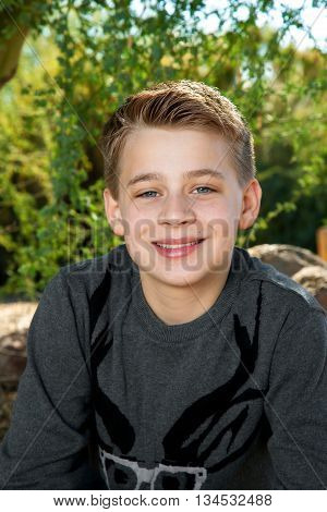 Portrait of a blond tween boy smiling at the camera outdoors.