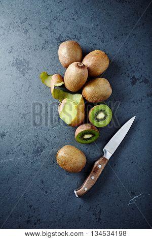 An Arrangement of Kiwi Fruits on a Black Stone