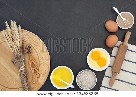 Bread baking ingredients and utensils with wheat sheaths and grain in a love spoon on grey slate background.
