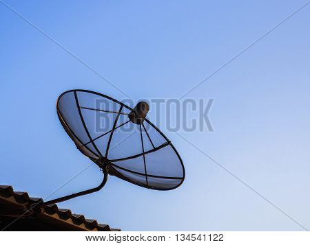 Satelite dish for digital television signal on the roof ot the house with blue sky for copy space