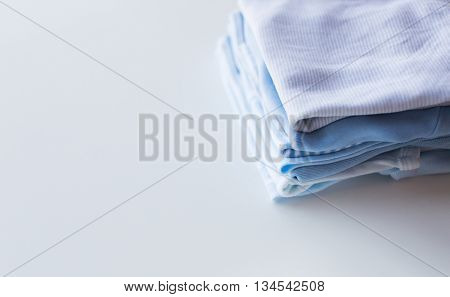 clothing, babyhood, motherhood and object concept - close up of pile of baby clothes for newborn boy folded on table
