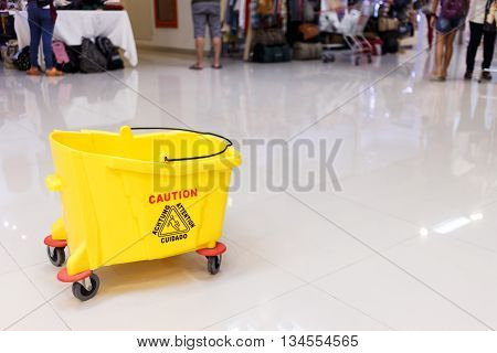 Mop bucket and caution sign on wet floor at shopping mall