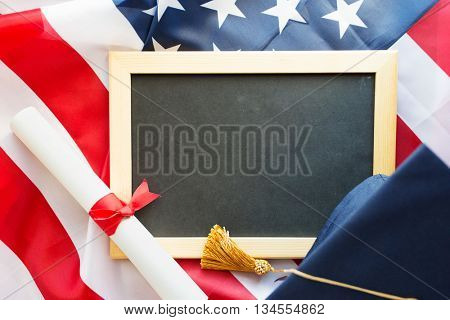 education, graduation, patriotism and nationalism concept - close up of bachelor hat, blackboard and diploma on american flag