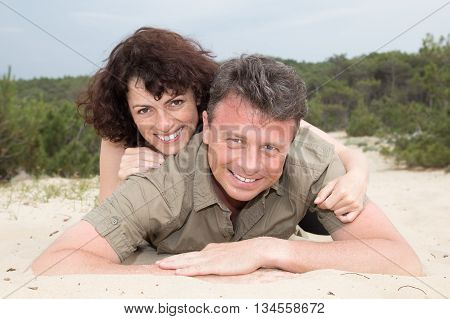 Middle-aged Couple At The Beach On The Sand On Holidays