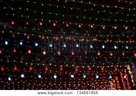 A background of colorful light wires setup high for decoration during a festival.
