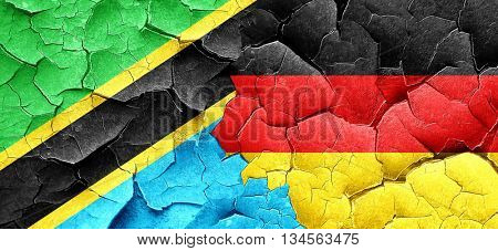 Tanzanian flag with Germany flag on a grunge cracked wall