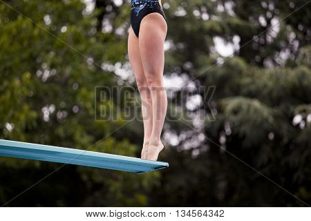 Lady diver preparing to jump from the springboard